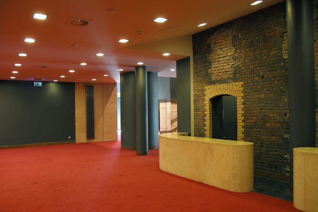 Wnętrze korytarz teatru. Czerwony kolor sufitu i podłogi, filary w kolorze szarym.